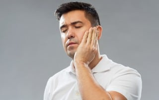 Unhappy man, suffering from jaw pain