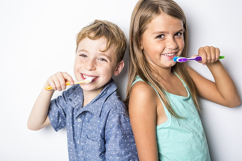 Two young children brushing their teeth while smiling. A recent study shows that children like these are getting to much fluoride