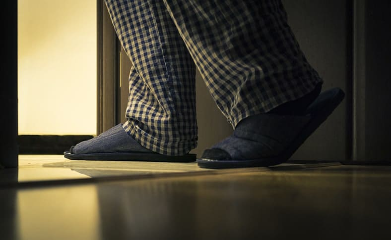 Adult man in pajamas and slippers walks to a bathroom at the night. Sleep Apnea can cause frequent urination at night.