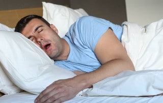 Man laying on his side with mouth wide open. The fluid in his throat might be causing his snoring