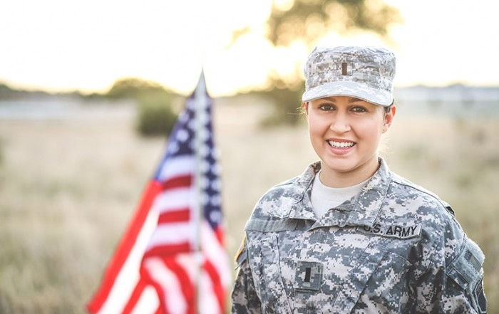 Beautiful Army Woman in Uniform with Flag. Like 83% of Americans, she is prioritizing oral health.