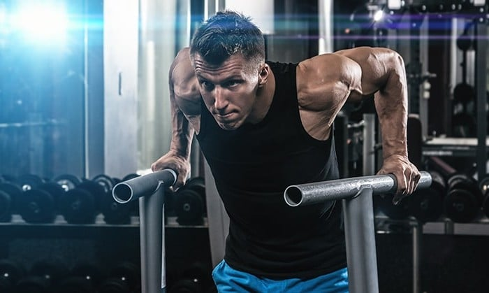 Man doing workout in a gym. Are his muscles causing migraines?