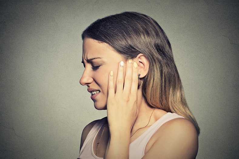 Side profile of a young woman suffering from Tinnitus, or is it TMJ. Researchers have found modulation is an important clue to diagnosis and treatment.