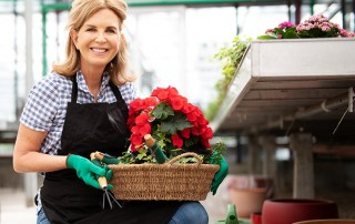 Middle aged blonde woman in plaid shirt and jeans enjoys the outdoors, tending to flowers. While working in the public, it's important to have a great smile but a chipped tooth might add to insecurities.
