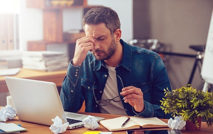 Man in denim shirt sits at his work laptop, exhausted from the day. Due to lack of rest because of sleep apnea he's suffering from 1 of 7 Symptoms of Sleep Apnea You Shouldn't Ignore.