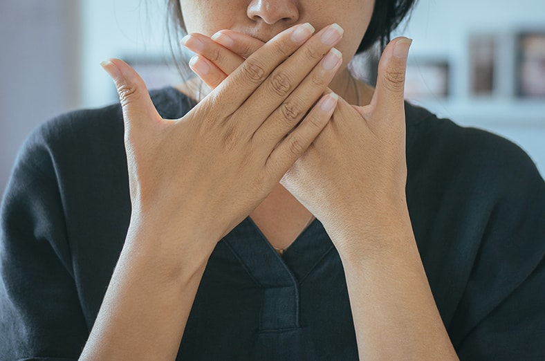 Asian woman covering her mouth, ready to gag. When gagging is preventing you from taking care of your teeth for routine dental visits, it's time to learn more about the options at River Edge Dental.