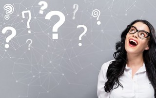 Question Marks with happy young businesswoman on a gray background. Do you have unaswered questions about porcelain veneers? Our dentists at River Edge Dental have all of the answers to the top porcelain veneers FAQs.