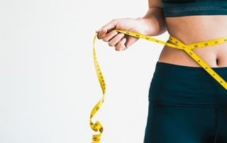 Closeup of a woman with a tape measure, checking her weight loss