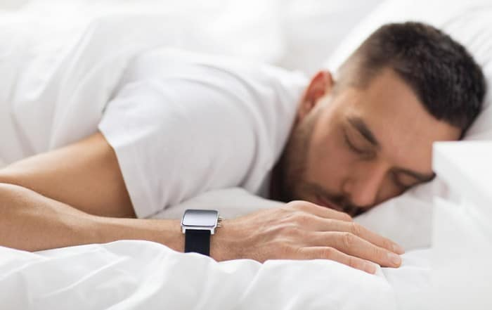 Man rests peacefully in bed with his smartwatch tracking his sleep
